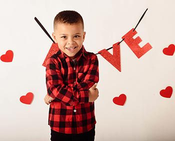 Young Maddox stands in front of Love and hearts sign